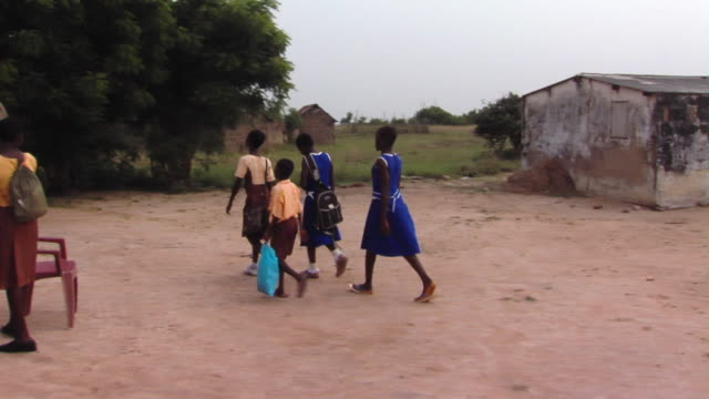 ms pan school children passing by man and teenage girl standing outside mud hut, tamale, ghana - shack stock videos & royalty-free footage