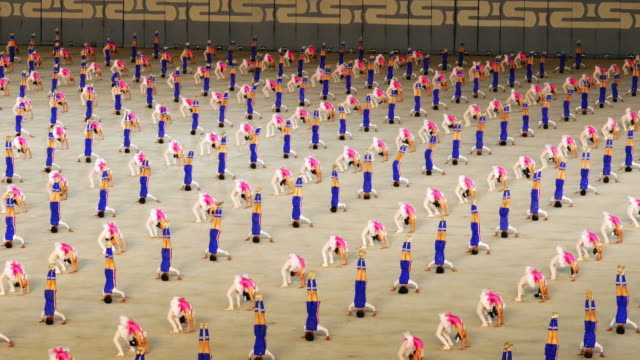 school children performing amazing synchronised gymnastics during mass games in pyongyang, north korea, dprk. medium shot - north korea stock videos & royalty-free footage