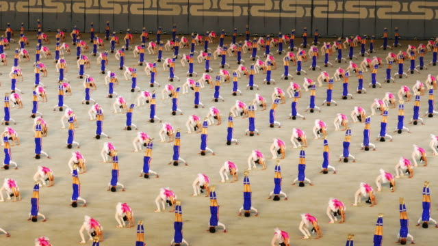 school children performing amazing synchronised gymnastics during mass games in pyongyang, north korea, dprk. medium shot - spoonfilm stock-videos und b-roll-filmmaterial