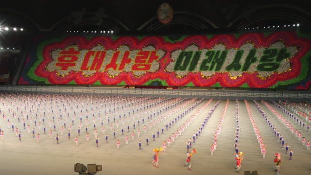 school children performing amazing synchronised gymnastics during mass games in pyongyang, north korea, dprk. wide shot - spoonfilm stock-videos und b-roll-filmmaterial