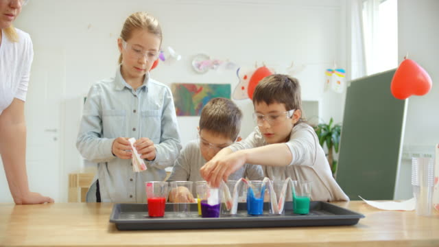ds school children placing paper towel strips into cups with colored water for a science experiment - wearing a towel stock videos & royalty-free footage