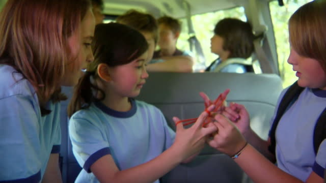 ms, school children (8-11) playing cats cradle sitting in van, bovina, new york state, usa - cat's cradle stock videos & royalty-free footage