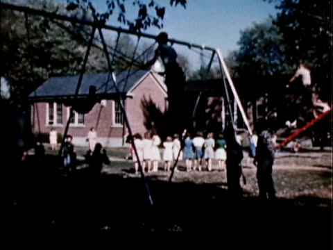 vídeos de stock e filmes b-roll de 1956 ws pan school children playing in playground / usa - menos de 10 segundos
