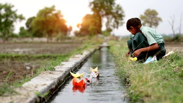 紙の船は運河の近くで遊ぶ児童 - おもちゃ点の映像素材/bロール