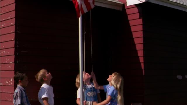 School children raise an American flag.