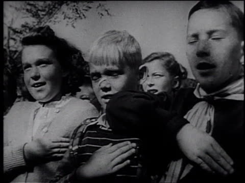 1945 montage school children reciting the pledge of allegiance to an american flag / united states - frank capra video stock e b–roll