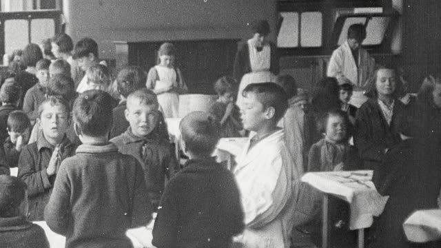 vídeos y material grabado en eventos de stock de 1925 montage school children standing in cafeteria with hands clasped in prayer, lunch being served by fellow students wearing white coats, and students sitting at table eating from steaming bowls of soup / newcastle upon tyne, england, united kingdom - comida escolar