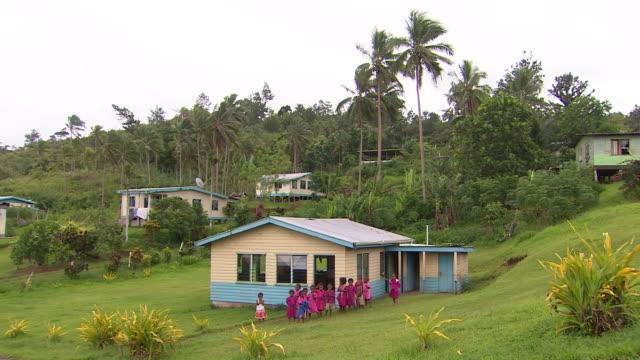 school children standing outside classroom in village of naviavia, fiji. - village点の映像素材/bロール