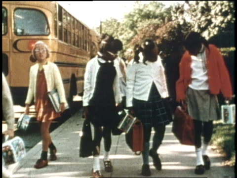 vidéos et rushes de school children walk on a sidewalk near a school bus - 1970
