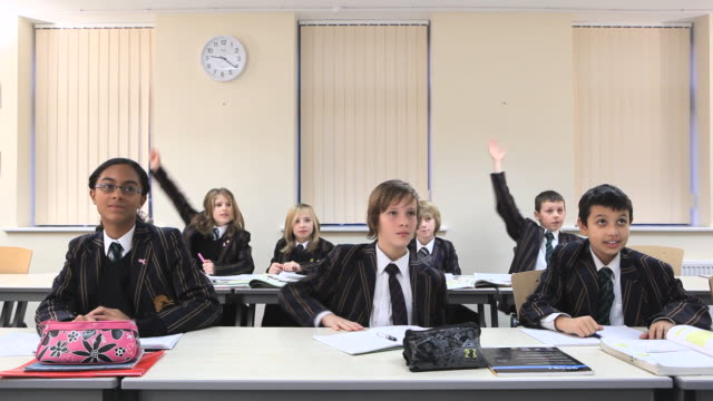 WS School children wearing blazers sitting at desks in two rows, holding up hands for answer to questions / Bristol, United Kingdom