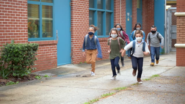 school children with face masks running outside building - 8 9 years stock videos & royalty-free footage