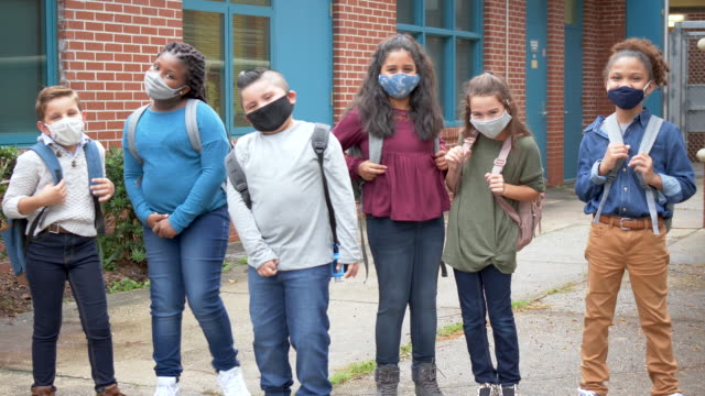school children with face masks standing outside building - 10 11 years stock videos & royalty-free footage