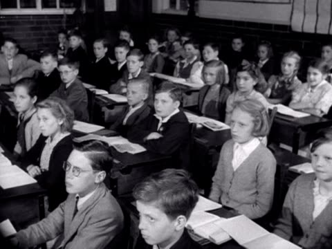 vídeos de stock e filmes b-roll de school children work in a classroom - 1955