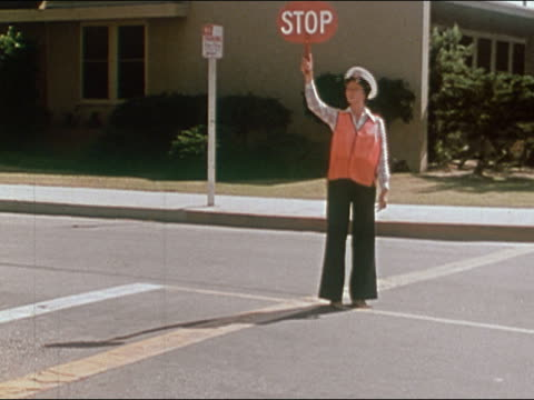 1978 school crossing guard holding stop sign / looking for traffic / waving for students to cross - stop sign stock videos and b-roll footage