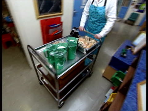 school food experiment; itv evening news: sue saville england: hampshire: shipton bellinger primary school: int dinner lady towards with trolley of... - itv evening news stock-videos und b-roll-filmmaterial