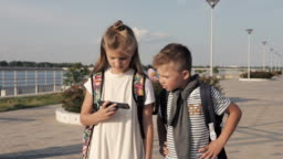 School friends boy and girl walking and looking into smartphone
