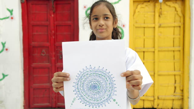 school girl displaying her piece of art that she sketched rangoli henna pattern complex handmade standing in front of a red and a yellow door and looking at the camera present show proud - indian ethnicity stock videos & royalty-free footage