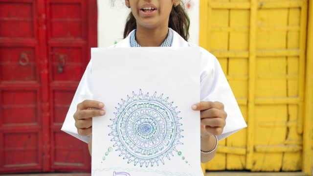 school girl displaying her piece of art that she sketched rangoli henna pattern complex handmade standing in front of a red and a yellow door and looking at the camera present show proud - pencil icon stock videos & royalty-free footage