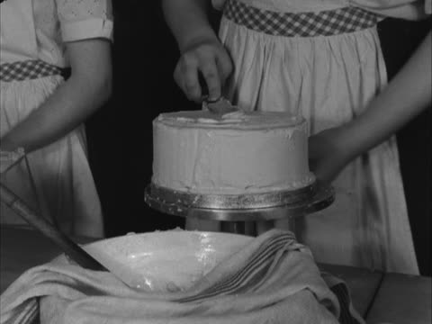 stockvideo's en b-roll-footage met school girl ices a cake during a cookery class. - home economics