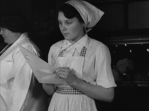 stockvideo's en b-roll-footage met school girl makes a piping bag out of paper during a cookery class. - home economics