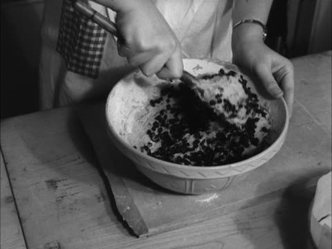 stockvideo's en b-roll-footage met a school girl mixes cake mix in a bowl during a cookery class - huishuidkunde