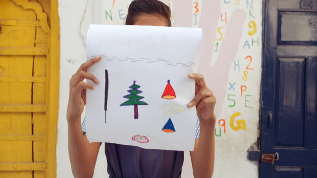 school girl shows her sketch drawing of christmas tree and santa hat on a piece of paper for presentation as she stands in front of a yellow and a blue door - pencil icon stock videos & royalty-free footage