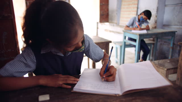 school girl wearing a mask is writing intently as she is studying and taking notes in her notebook - school building stock videos & royalty-free footage