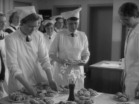 stockvideo's en b-roll-footage met school girls present their finished hot cross buns to their teacher during a cookery lesson - huishuidkunde