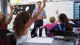 School kids raising hands in an elementary school class