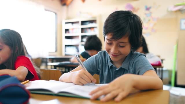 vidéos et rushes de enfants d'école écrivant une dictée dans la salle de classe - carnet