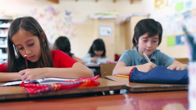 vídeos de stock e filmes b-roll de school kids writing a dictation in classroom - soletrar