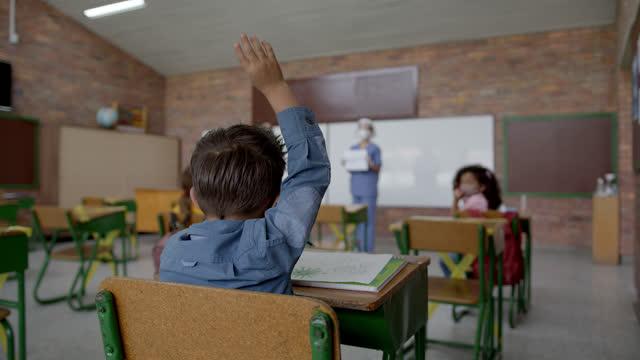 vídeos y material grabado en eventos de stock de enfermera de la escuela respondiendo a una pregunta sobre las pautas covid-19 al estudiante que levantó la mano - edificio escolar