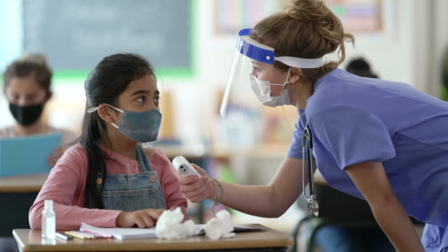 school nurse checking students temperature - pacific islander teacher stock videos & royalty-free footage