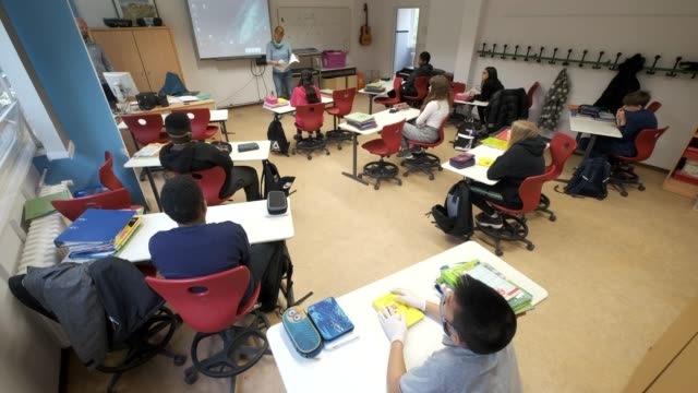 vídeos de stock e filmes b-roll de school principal catrin herfet-sternberger welcomes sixth graders, who are sitting at desks socially-distanced, on the first day of classes since... - escola primária