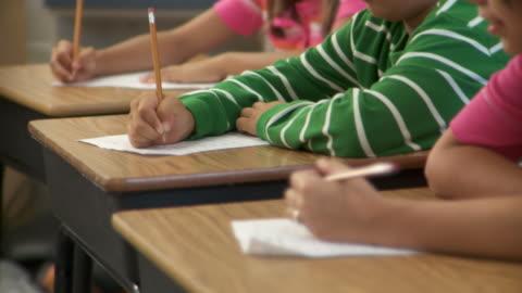 vídeos y material grabado en eventos de stock de cu, pan, school pupils (8-11) taking notes in classroom, richmond, virginia, usa - examen