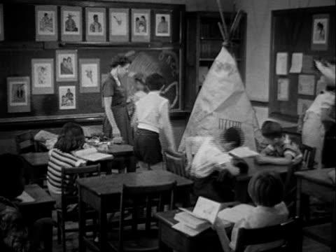 school room w/ teacher talking w/ students, boy holding native american headdress [sot dr. spock saying good school, trained teacher, small class... - headdress stock videos & royalty-free footage