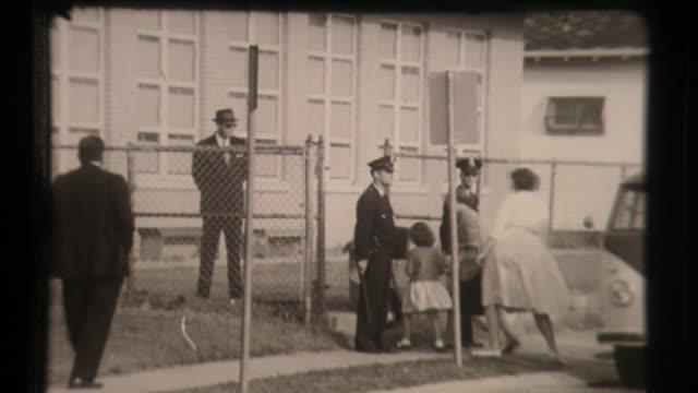 vídeos y material grabado en eventos de stock de school segregation, parents drop off kids, police escort kids to school, civil rights education desegregation - separación