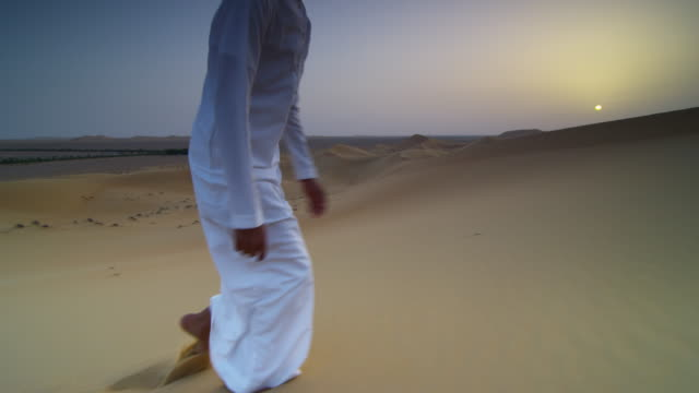 school student climbs sand dune on desert field trip, uae - bbc stock videos and b-roll footage
