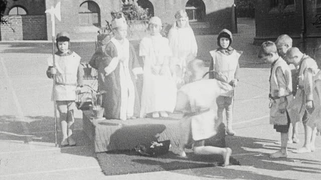 1925 MONTAGE School students dressed in period costumes performing outdoor historical drama scene of Queen Philippa begging King Edward III to spare the lives of the men of Calais / Newcastle upon Tyne, England, United Kingdom