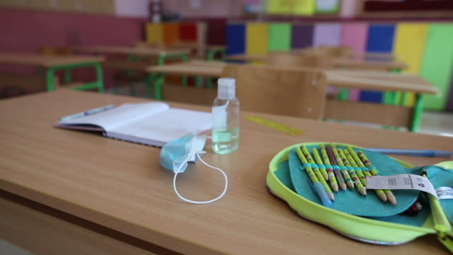 school supplies, face mask and hand sanitizer on desk at elementary school classroom - school supplies stock videos & royalty-free footage
