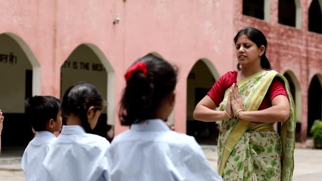 School teacher praying with students, Haryana, India