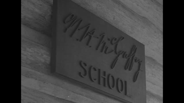school teacher rings bell in front of mcguffey log school / sign w h mcguffey school / children running from marthamary chapel with henry ford... - school bell stock videos and b-roll footage