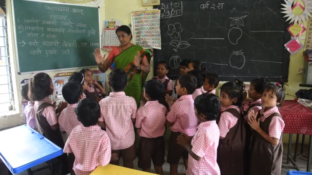 school  teacher teaching to indian rural school student, maharashtra, india. - grundschüler stock-videos und b-roll-filmmaterial