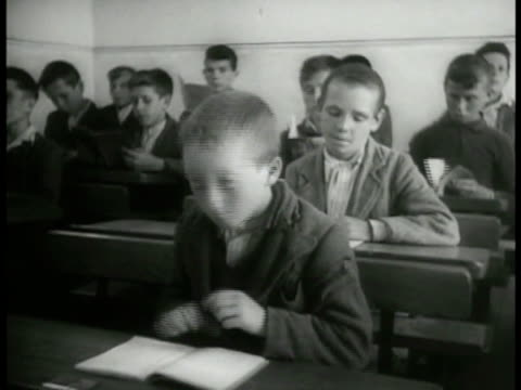 school w/ children sitting in desks irish boy sitting at desk w/ others sitting bg cu page in open gaelic book gaelic amp english sign 'rushbrook'... - directional sign stock videos & royalty-free footage