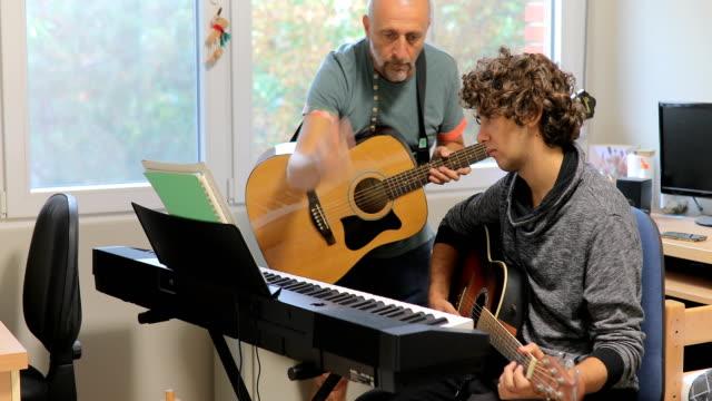vídeos y material grabado en eventos de stock de schoolboy y profesor tocando la guitarra en la sala de estar - guitarra