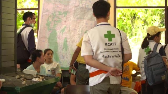 rescuers race against time as monsoon rains near thailand chiang rai int medics standing family members sitting - 洞窟点の映像素材/bロール