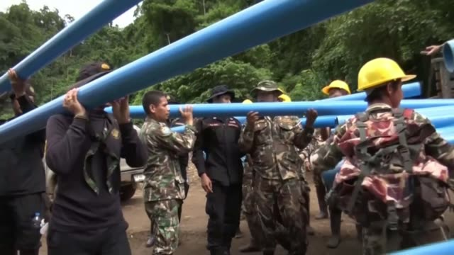 Rescuers race against time as monsoon rains near THAILAND Chiang Rai EXT Various of soldiers taking pipes from flatbed trucks Water flowing into...