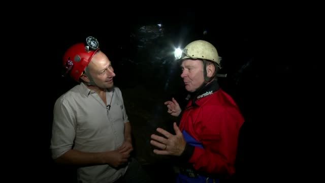 Two British divers first to discover schoolboys WALES Martyn Farr and reporter along through cave Torch on helmet as along **Farr interview partly...