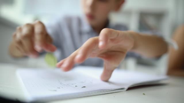 自宅で宿題のためのノートパッドに鉛筆で描く男子生徒 - 消しゴム点の映像素材/bロール