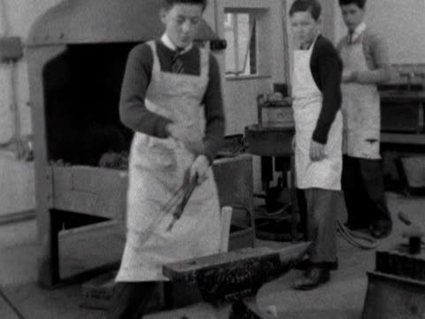 A schoolboy hammers a piece of metal on an anvil in a metalwork class 1958